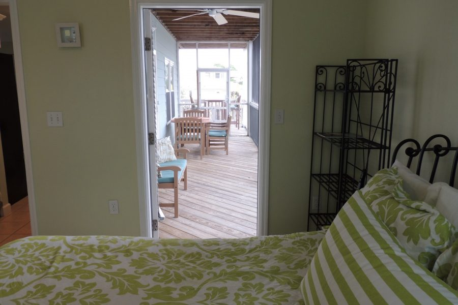 King Bedroom Off of Kitchen/Main Floor Facing the Gulf, View of Screened-In Porch with Door Open